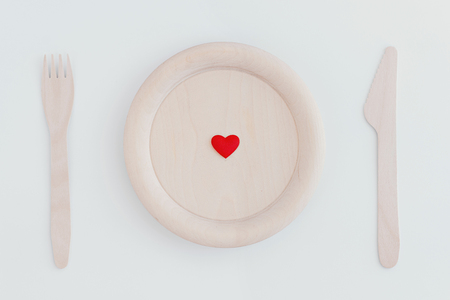Small red heart on wooden plate, fork and knife on white background. Top view. Zero waste concept.