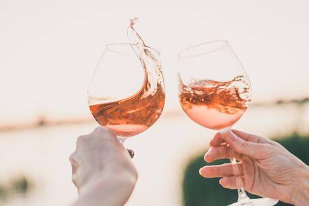 Dos copas de vino rosado en las manos contra el cielo del atardecer. Recortada. Foto de archivo