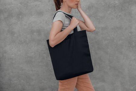 Jonge vrouw met zwarte katoenen tas in haar handen op grijze achtergrond. Bijgesneden. Stockfoto