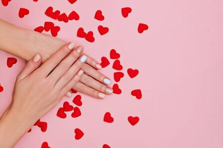 Woman's hands with pastel manicure on pink background with red hearts. Valentine's day concept. Place for text. 版權商用圖片