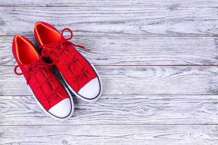 New red sneakers on wooden background with copy space. Top view.