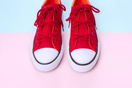 New red sneakers on pink and blue background with copy space. Top view.