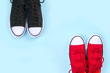 New black and red sneakers on pale blue background with copy space. Top view. Stockfoto