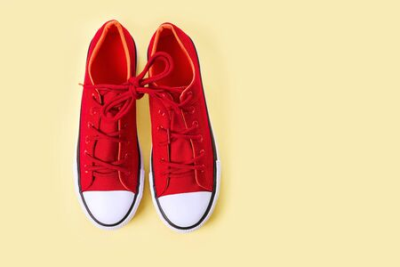New red sneakers on yellow background with copy space. Top view.