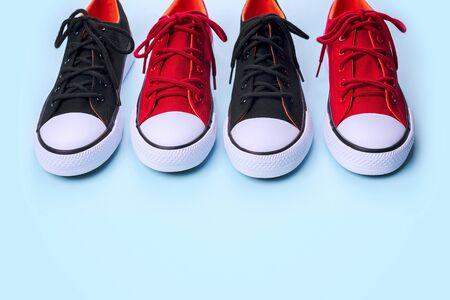 New black and red sneakers on pale blue background with copy space.