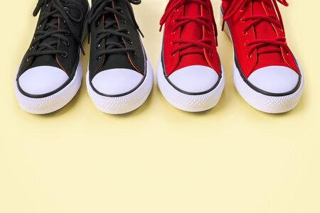 New black and red sneakers on yellow background with copy space.