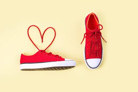New red sneakers with shoelaces shaped heart on yellow background with copy space.