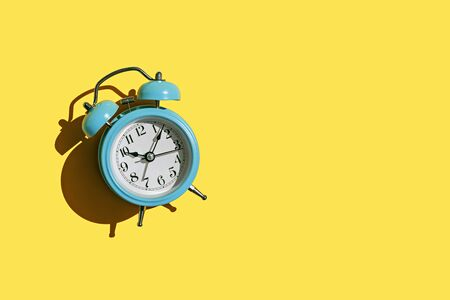 Blue alarm clock on yellow background with copy space. Top view. Banco de Imagens