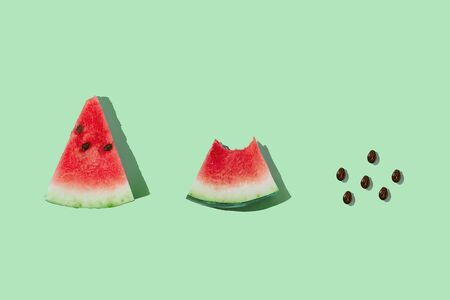 Slice of ripe watermelon and seeds on mint green background with copy space. Process of eating watermelon from whole slice to seeds. Flat lay, top view.
