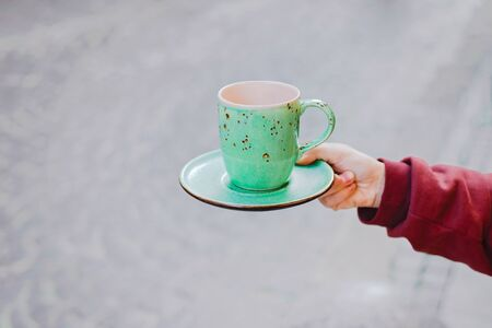 Big mint green tea cup in womans hands with pastel manicure. Cropped. Stok Fotoğraf