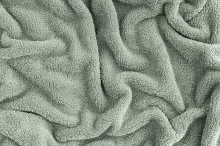 Close up top view of coral blanket wrinkled texture. Fluffy mint tranquil green background. Top view.