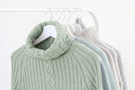 Tranquil mint green knitted warm sweaters on white hangers. Close up. Stok Fotoğraf