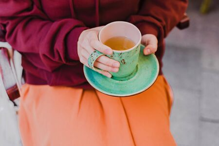 Big mint green tea cup in womans hands with pastel manicure while sitting in cafe. Cropped.