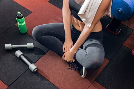 Woman at gym is sitting on the floor with dumbells after workout.
