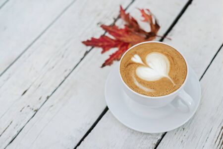 White big cup of coffee with art on white wooden table and autumn leaves with copy space. Top view.