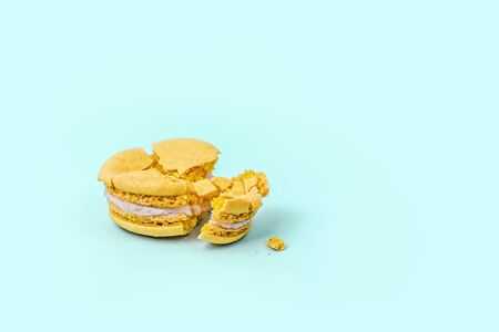 Crushed yellow macaroon on pastel blue background with copy space. Top view. 写真素材