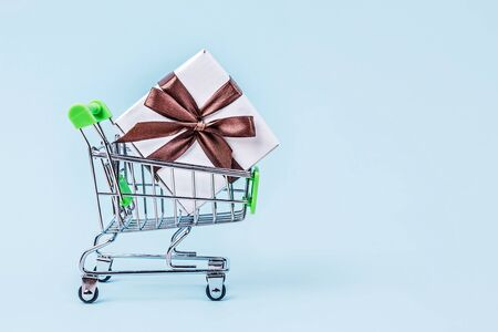 Gift box with brown bow in miniature shopping cart on pastel blue background with copy space. Shopping concept.