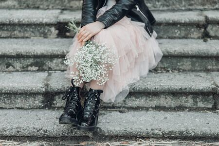 Woman in pink lace skirt with white flowers bouquet in her hands is sitting on stairs. Cropped. 写真素材