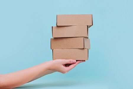 Womans hands holding boxes stacked on blue pastel background. Mock up, copy space.