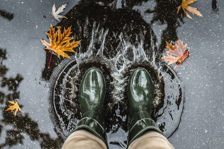 Feet in olive green rubber boots standing in a puddle with fallen leaves and making splashes. Autumn concept.