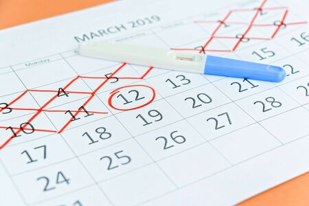 Pregnancy test with circling date in calendar. Planning of pregnancy, trying to have baby.