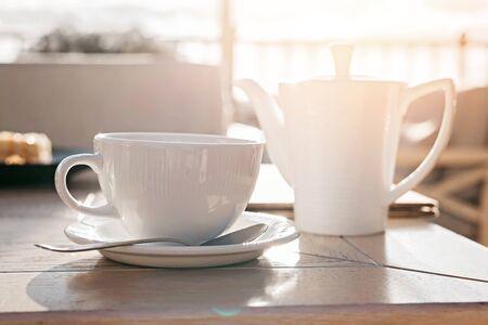 Weiße große Tasse köstlichen Kaffee auf Holztisch im Abendlicht mit Kopienraum. Lifestyle-Ansicht.