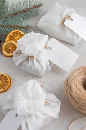 Christmas presents wrapped with white furoshiki fabric, labels and dried orange slices. Eco friendly gift, zero waste concept.