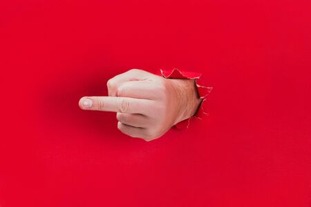 Male hand shows a sign of middle finger through a hole in red background.