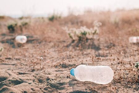 Plastic bottles waste on a beach. Earth pollution concept. Copy space.
