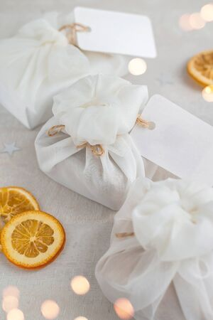 Christmas presents wrapped with white furoshiki fabric, labels and dried orange slices. Eco friendly gift, zero waste concept. Stock fotó