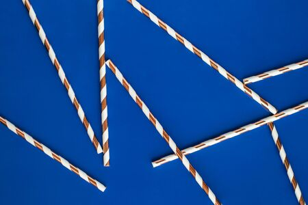 Background made of coctail straws with golden stripes on blue color. Top view.