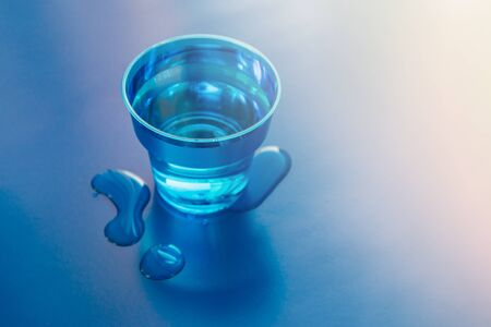 Filled blue glass of water on blue neon background with spilled water on it. Copy space.