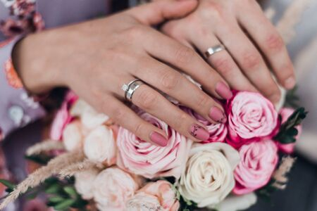 A romantic couple holding hands with wedding rings. Cropped. Standard-Bild