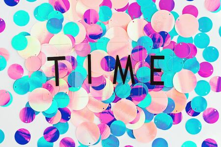 Background with shiny pink, purple and holographic sequins with word Time, abstract background. Top view.