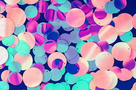 Big round holographic sequins abstract colorful background. Top view.