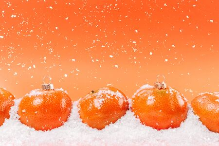 Banner with a mandarin in the form of a Christmas tree toy in the snow, with falling snow. An orange background with empty space for a test. Christmas or New Year