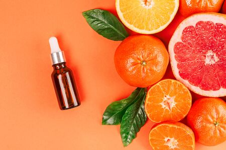 Fresh ripe mandarins, grapefruit and oranges with green leaves and glass bottle with essential oil on orange background. Top view.