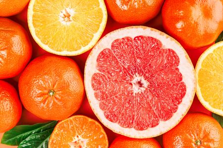 Fresh ripe mandarins, grapefruit and oranges with green leaves on orange background. Close up, top view. Stock Photo