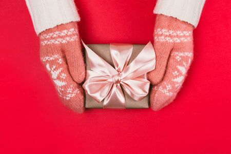Woman's hands in warm knitted mittens hold gift box wrapped with craft paper and pink ribbon on red background. Festive concept. Place for text. Stock Photo