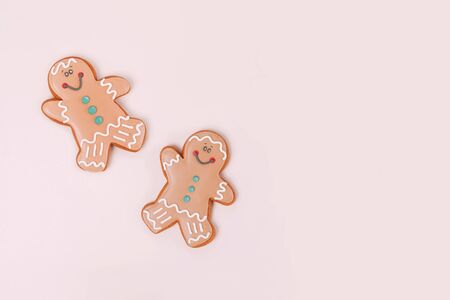 Couple of ginger cookies on pale beige background with copy space. Top view.