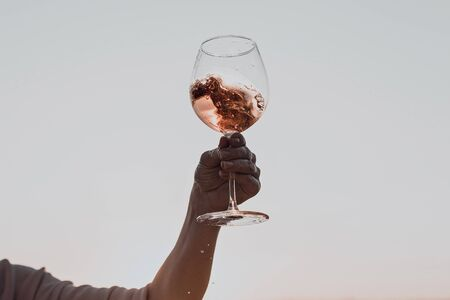 Glass of wine with splashes in womans hand against the sunset sky. Stockfoto