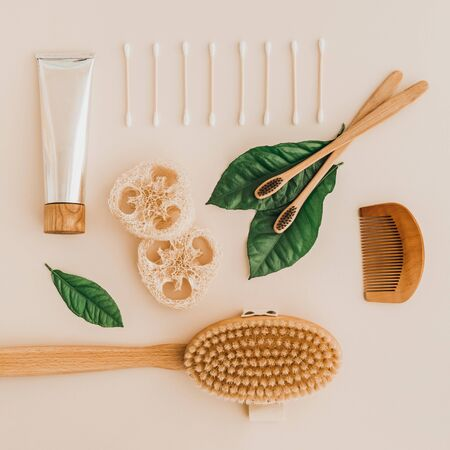 Bamboo toothbrush, toothpaste, natural brush, self-care cosmetics products and white cotton mesh bag on pale background. Zero waste and plastic free concept.