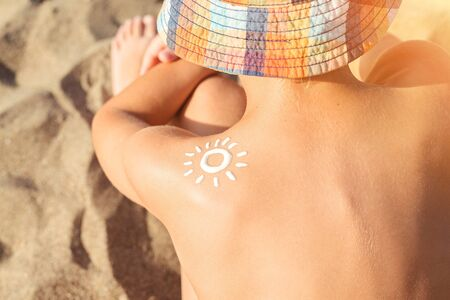 Sun lotion on taned kid's shoulder, close up view. Sun protection.