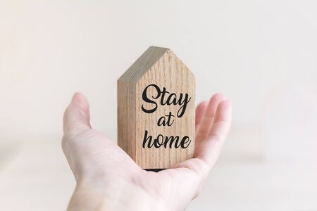 Small wooden toy house in hand on white pastel background with words stay at home. Quarantine concept. Imagens
