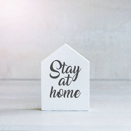 White wooden toy house on white pastel background with words stay at home. Quarantine concept.