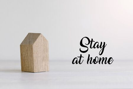 Small wooden toy house on white pastel background with words stay at home. Quarantine concept. Imagens