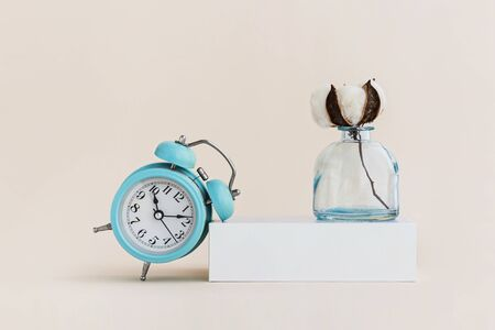 Beautiful white cotton flower in vase and alarm clock. Minimal monochrome creative picture. Concept.