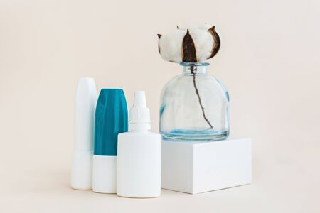 Creative picture of bottles of nose drops for treatment various viruses symptoms or seasonal allergic rhinitis with cotton flower in vase. Healthcare concept. Imagens
