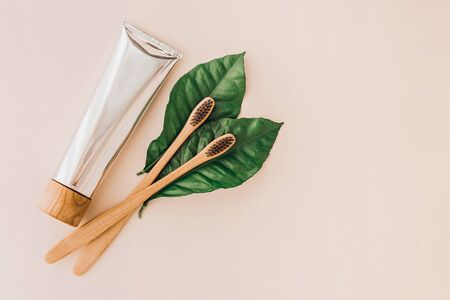Bamboo natural toothbrushes, toothpaste and fresh leaves on pale background. Zero waste and plastic free concept. Sustainable lifestyle concept.