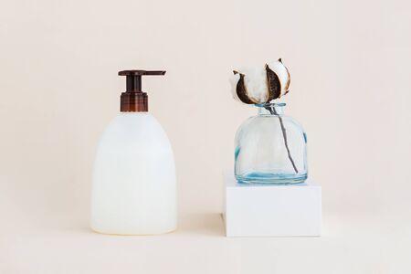 Liquid soap and cotton flower. Minimal organic and zero waste cosmetics concept. Monochrome.